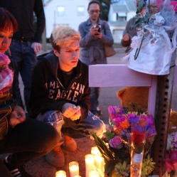 Anthony Burgio, left, with family friend Sarah Wilbur, place flowers and candles in memory of Burgio's sister Brittany, who was struck by a car Tuesday on Dewey Avenue.